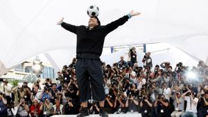 FILE PHOTO: Former soccer star Diego Maradona balances a ball on his head during a photocall for