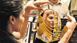 A woman looks at a gold necklace in a jewellery shop in Noida in this file photo.(Virendra Singh Gosain/HT Photo)