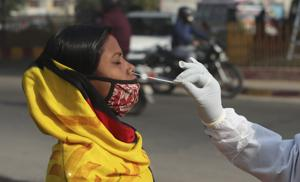 A health worker takes nasal swab sample of a woman to test for COVID-19 in Jammu.(AP)