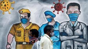 Men walk past a mural of frontline workers amid the spread of the coronavirus disease in Mumbai, India.(REUTERS)