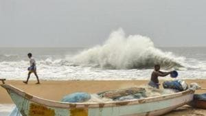 Cishermen work at a beach in the backdrop of a rough sea due to Cyclone Amphan, at Mamallapuram in Chengalpattu district.(PTI)