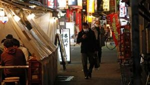 People wearing protective face masks walk past at a Japanese izakaya pub alley, amid Covid-19 outbreak, in Tokyo, Japan.(REUTERS)