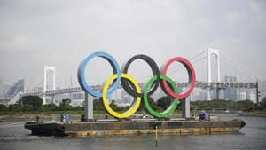 the Olympic rings for the Olympic and Paralympic Games Tokyo 2020 pass by on a barge by tugboats off the Odaiba Marine Park in Tokyo.(AP)