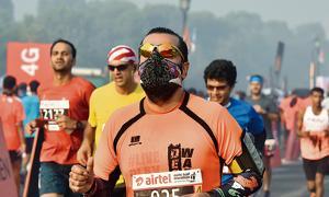 A participant runs wearing a mask in the Airtel Delhi Half Marathon 2016 in New Delhi on November 20.