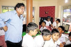 Prof Mitra supervises children at a SOLEcentre.