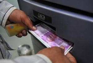 A man takes out Rs 2,000 banknotes from an ATM  in November 2016. The government's decision to replace 1,000 and 500 rupee banknotes with new 2,000 rupee notes has upset the country's cash flow.