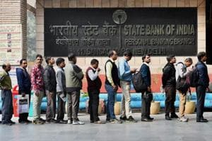 People stand in line outside a bank to withdraw cash in New Delhi.