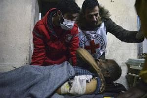 This photo released by the International Committee for the Red Cross on Wednesday, shows members of the Syrian Arab Red Crescent laying a patient on stretcher after taking him out of a medical facility in the Old City of Aleppo in Syria.