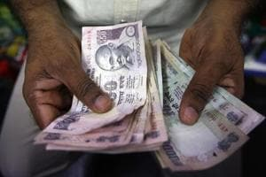 A private money trader counts rupee notes at a shop in Mumbai.