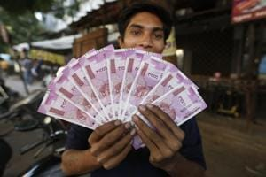 A man displays new currency notes in Ahmadabad/