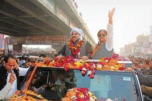 Atiq Ahmed (L) greets supporters on way to rally venue in Kanpur on Thursday.