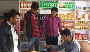 A resident swipes to pay at a grocery shop in Palakhede village in Agar district on Wednesday.