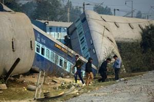 Officials and bystanders gather at the derailed train carriages at Rura, some 30 kms west of Kanpur on December 28, 2016, following a train crash in the northern Indian state of Uttar Pradesh.