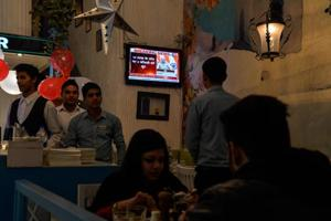 """Prime Minister Narendra Modi is seen on the television inside a restaurant as he address the nation on December 31. Modi had asked banks to """"keep the poor, the lower middle class, and the middle class at the focus of their activities"""" and to act with """"public interest"""" in mind."""