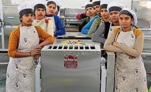 Workers engaged under the Annapurna Akshayapatra Yojana in the kitchen set up at Karuna Sadan, Sector 11, Chandigarh, on Tuesday.