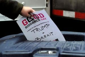 "A participant throws a piece of paper reading ""Trump and Brexit"" into a trash can to be shredded during ""Good Riddance Day"", New York City, December 28, 2016. Good Riddance Day is an annual event held in New York City for people to shred pieces of paper representing their bad memories or things they want to get rid of before the New Year."