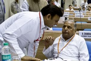 This file photograph taken in  2013 shows Uttar Pradesh chief minister Akhilesh Yadav (L) listening to his father Mulayam Singh at an event. In a country used to dynastic feuds, the battle between Akhilesh and his father Mulayam has been gripping stuff.