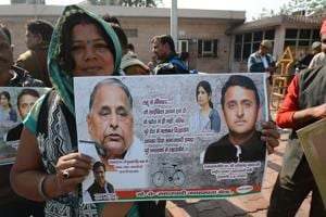 Samajwadi Party supporters hold posters and banners to campaign for party in Lucknow on Wednesday.