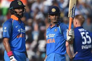 Mahendra Singh Dhoni raises his bat after completing his half century as Yuvraj Singh looks on during the second One Day International between India and England at the Barabati Stadium in Cuttack on Thursday.