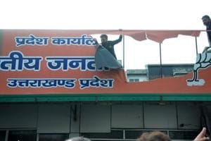 Protestors tear a hoarding at the BJP office in Dehradun on Tuesday.