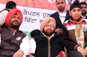 Punjab Congress chief Captain Amarinder Singh with party's Bathinda Rural candidate Harvinder Singh Laddi during a rally at Kotshamir village on Tuesday.