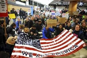 Protestors hold up an American flag at the airport.