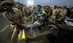 A protestor supporting Jallikattu tries to resist as police remove them from Chennai's Marina beach on January 23.