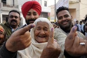 People showing ink mark after casting vote in Patiala on Saturday.