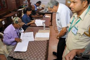 Defence minister Manohar Parrikar finding his name in the voter list at a polling booth in Goa on Saturday.