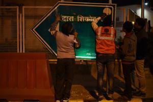 Workers change the name of Dalhousie Road to Dara Shikoh Road on Monday.