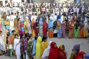 Voters stand in queues to cast their votes at a polling station during the fifth phase of UP assembly polls in Firozabad .