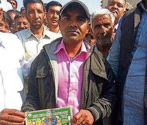 Azad Singh showing his lottery ticket and the lottery ticket number that matched.