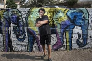 Artist Falko One poses with his mural near Mount Mary in Bandra