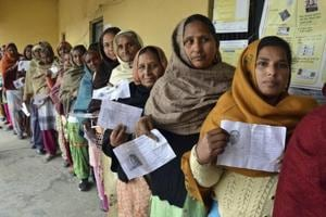 Women display their election identity cards as they stand in a queue to cast their votes outside a polling station, Chogawan, near Amritsar, Punjab, February 4.