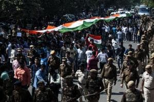 Students of the Akhil Bharatiya Vidyarthi Parishad (ABVP) are watched by security personnel as they shout slogans while carrying a giant Indian tricolour during a