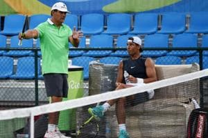 This file photo taken on August 1, 2016 shows Rafael Nadal of Spain listening to his coach and uncle Toni Nadal during a practice session at the Olympic park in Rio de Janeiro.