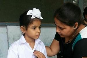A doctor examining a child during a medical checkup camp in Kapurthala.