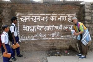 Md Mustafa writing slogans on the wall as school students pass by.