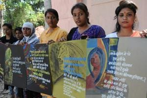 Students display placards at an exhibition on International Women