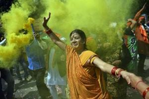 A supporter of BJP celebrates outside the party headquarters in New Delhi after the elections results were announced.