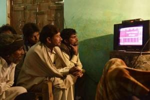 People in Jogayi Khera in Muzaffarnagar watching UP election results on television.