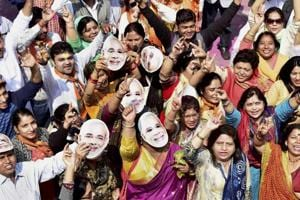 BJP workers and supporters, wearing the mask of Prime Minister Narendra Modi, celebrate the party's victory in the assembly elections, at party headquarters in New Delhi on Saturday.