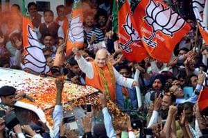 BJP president Amit Shah waves at party workers  on his arrival at the party headquarters, in New Delhi.
