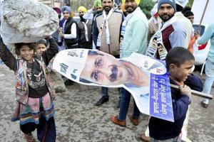 MISS THE CUT: Children carry a cutout of AAP leader Arvind Kejriwal at one of his road shows in Patiala for the Punjab assembly polls.