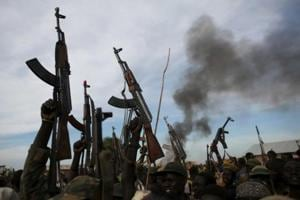 File photo of rebel fighters holding up their rifles as they walk in front of a bushfire in rebel-controlled territory in Upper Nile state, South Sudan, in February 2014.