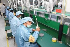 Staff working at the manufacturing line in a domestic smartphone production facility.