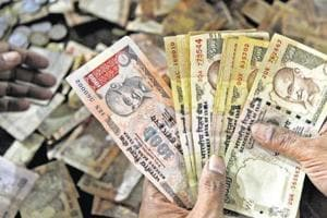 A man counting old Rs 500 and Rs 1,000 notes at a bank during demonetisation drive