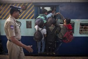 Passengers hang from the door of an overcrowded train in Hyderabad. Railway minister Suresh Prabhu will announce an ambitious plan to provide reserved berths to all train.
