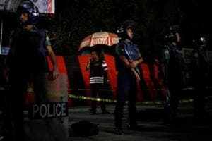 A security personnel talks over a walky-talky while others stand guard in front of the spot where a suicide bomber blew himself up near the Shahjalal International Airport in Dhaka, Bangladesh, on March 24, 2017.
