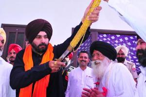 Punjab local bodies minister Navjot Singh Sidhu unsheathes a sword offered as a mark of honour by Congress workers during a thanksgiving visit to Mudhal village in his constituency Amritsar East on Sunday, March 26.